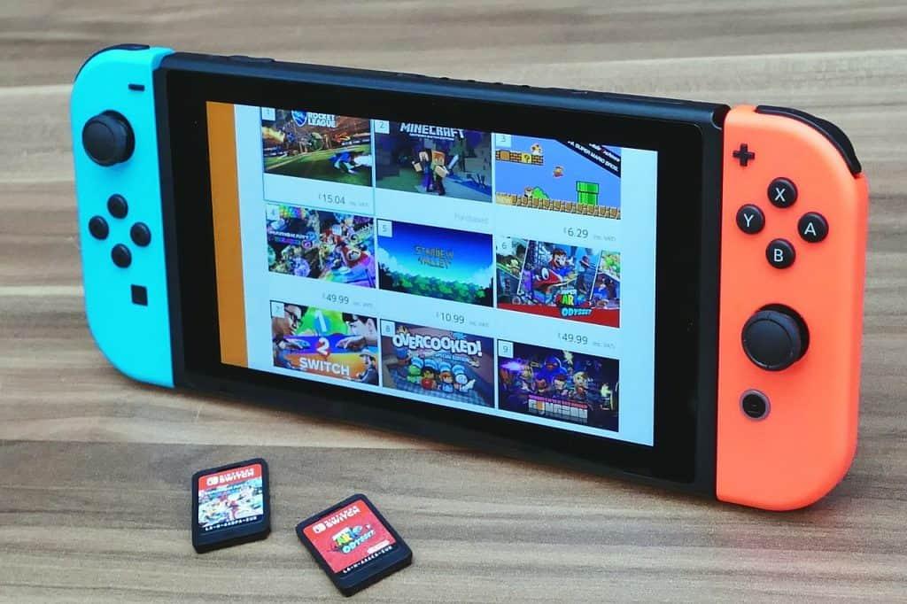 Imagem de Nintendo Switch e jogos sobre mesa.