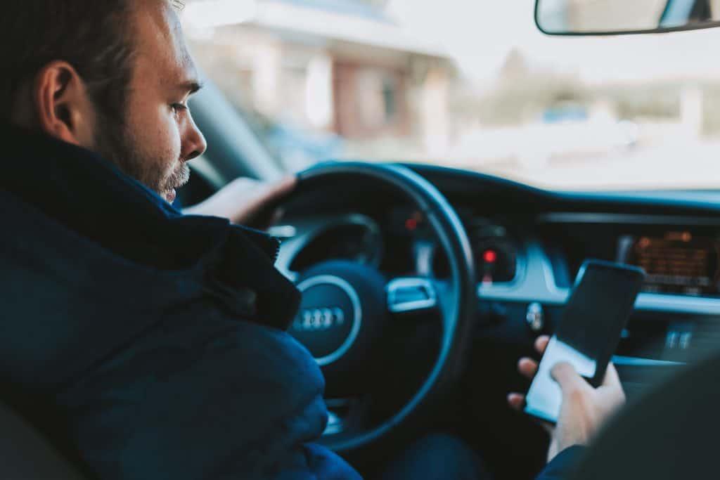 Imagem de pessoa com celular no carro.