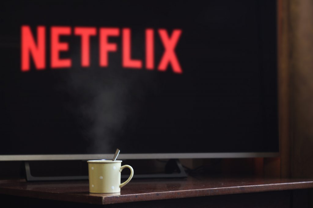 Imagem de mesa com caneca de café e televisor exibindo o logotipo do Netflix