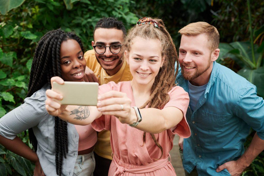 Imagem de um grupo de pessoas tirando uma selfie.