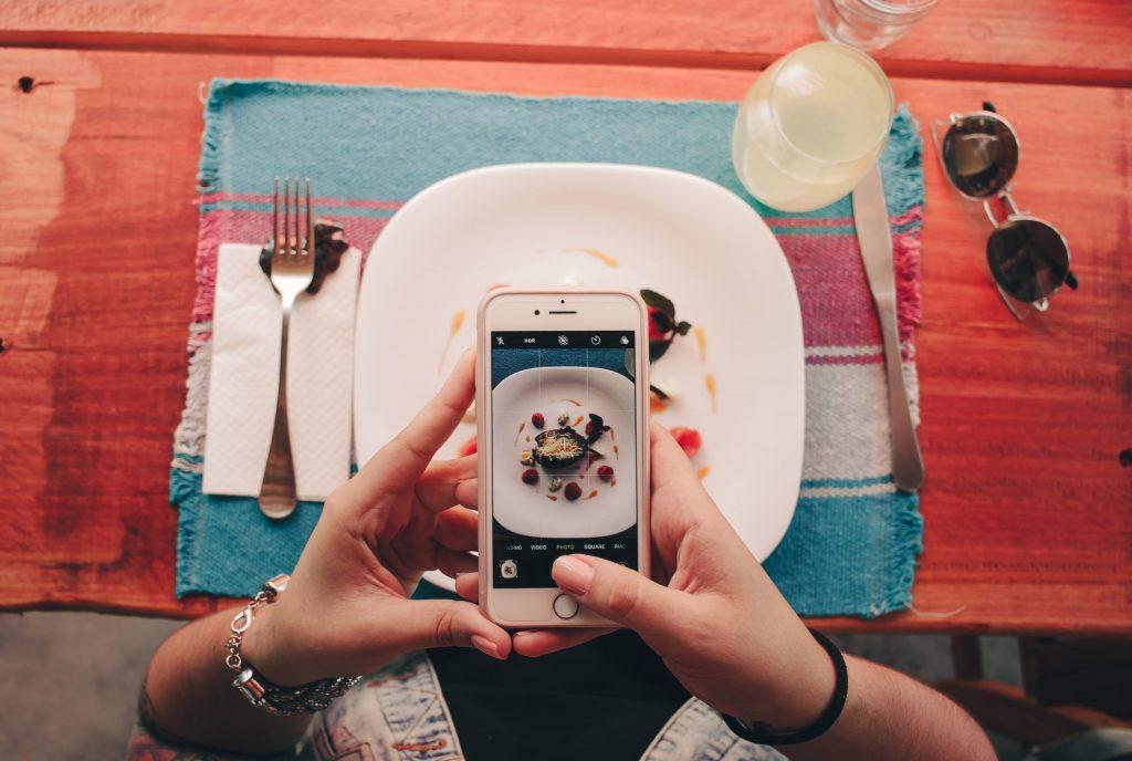 Imagem de uma pessoa fotografando a refeição.