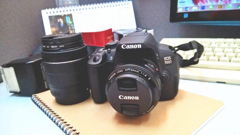 Câmera, lente e flash da Nikon sobre uma mesa.
