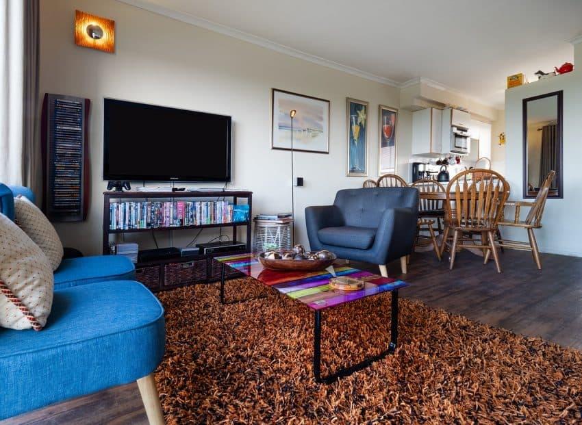 Imagem mostra a sala de uma casa e uma televisão de tela plana em cima de uma estante.