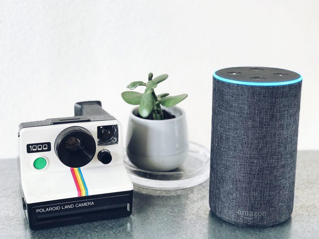 Imagem de uma dispositivo Echo ao lado de uma câmera instantânea.
