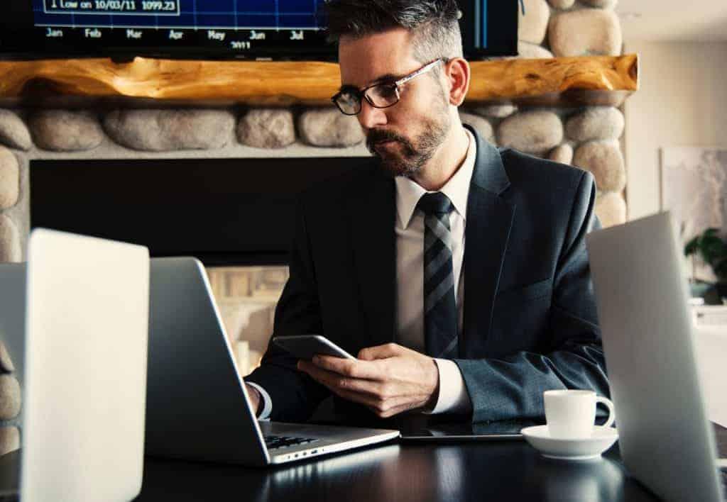 Na foto um homem de terno sentado em uma mesa olhando para um computador.