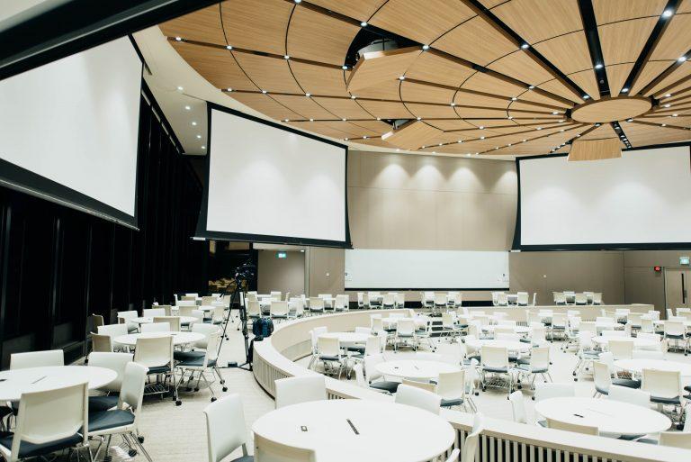 Imagem de sala de eventos com várias telas de projeção