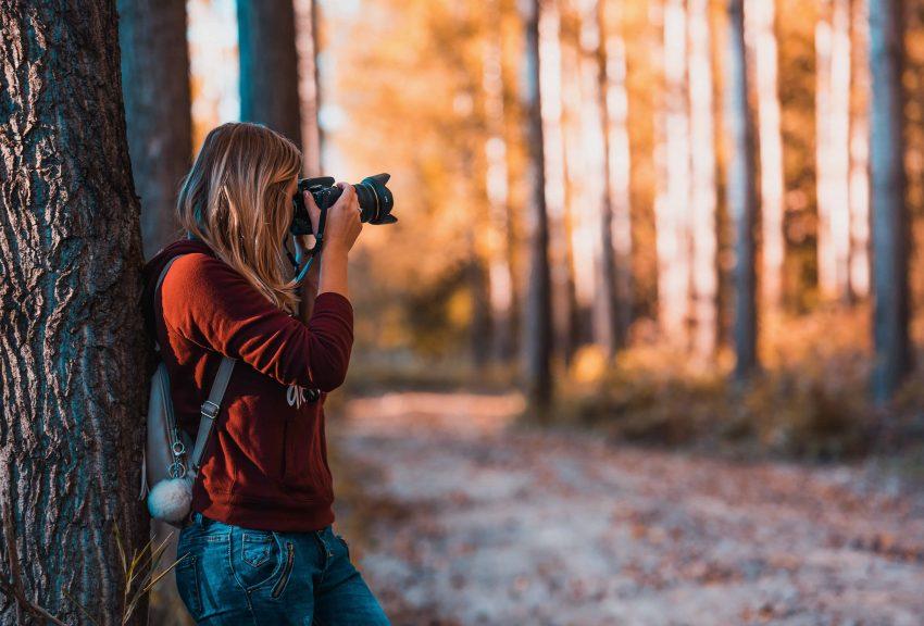 Na foto está uma fotógrafa com uma câmera tirando fotos de um parque.