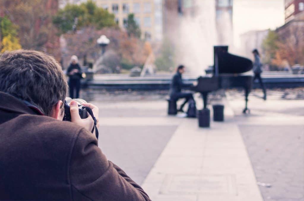 Na foto há um fotógrafo com uma câmera tirando uma foto de uma pessoa tocando piano em uma praça.