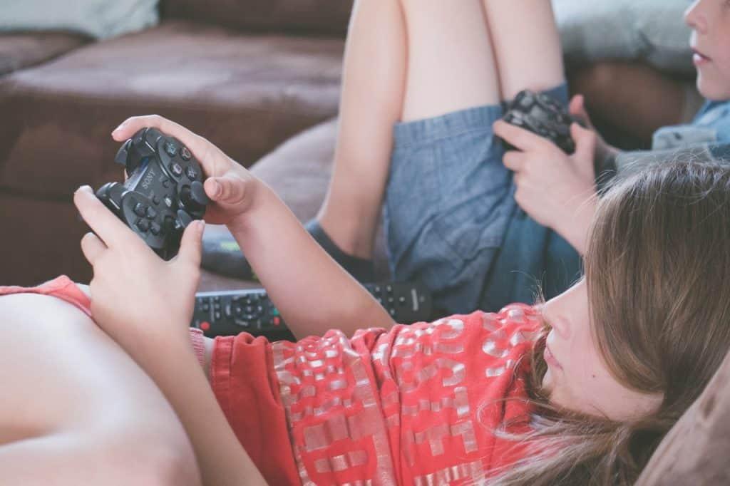 Imagem mostra duas crianças sentadas no sofá com controles de PlayStation 4 nas mãos.
