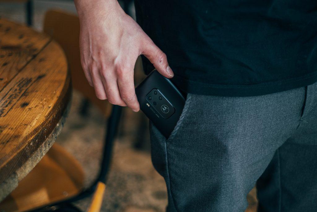 Imagem de um home guardando um celular no bolso.