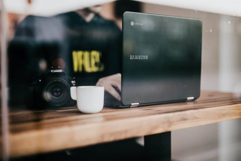 Pessoa teclando em notebook Samsung, com uma xícara e câmera fotográfica ao lado.