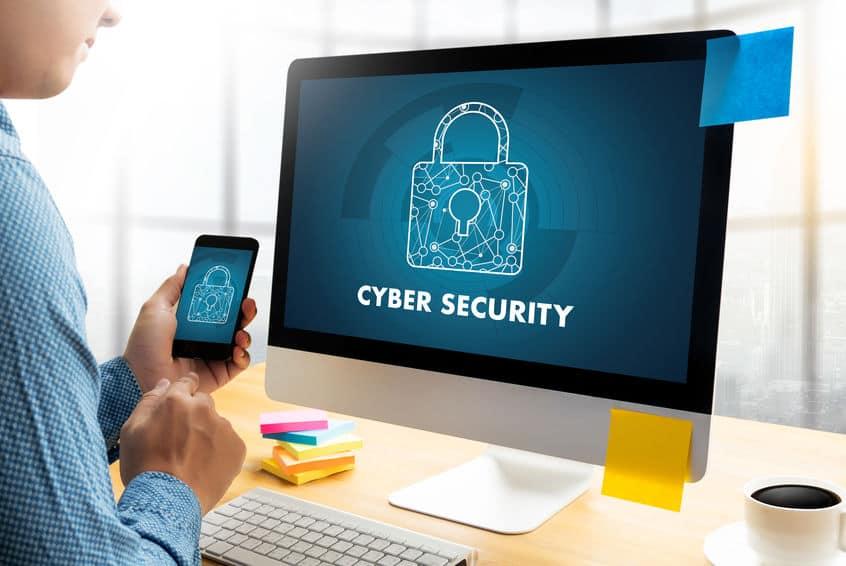 Imagem mostra um homem usando celular e computador com tela ligada em antivírus.
