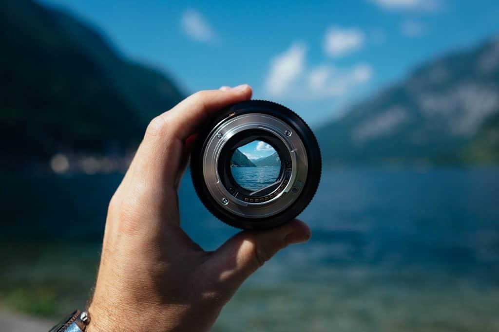 Na foto a mão de uma pessoa segurando uma lente de câmera em frente a uma praia.