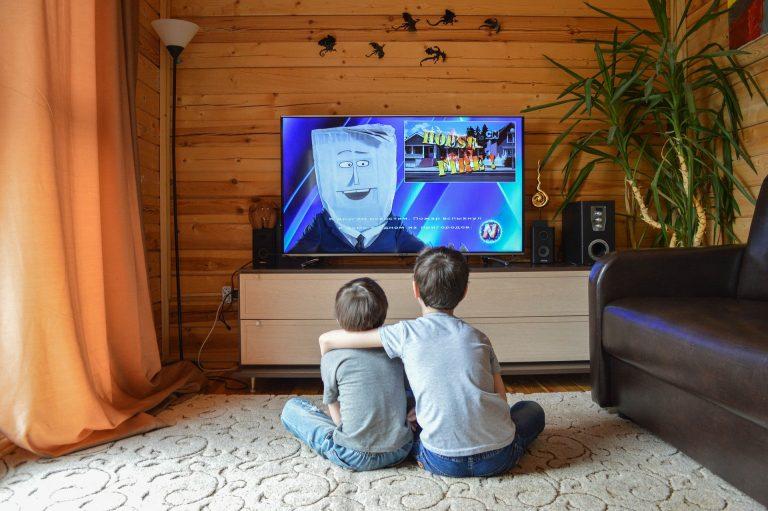 Duas crianças assistindo TV.