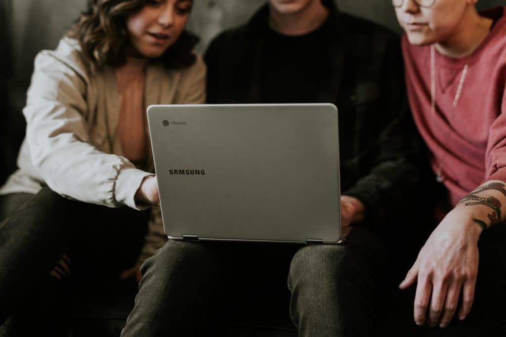 Três amigos sentados. Um deles no meio apoiando o notebook Samsung no colo.