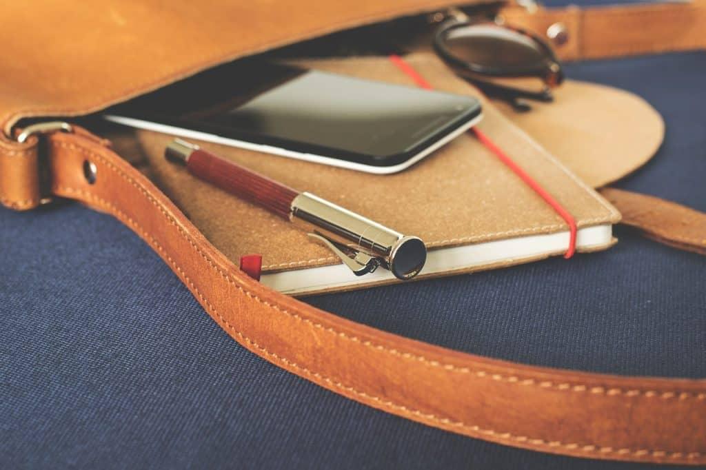 Bolsa com smartphone, caneta, caderno e óculos escuros.
