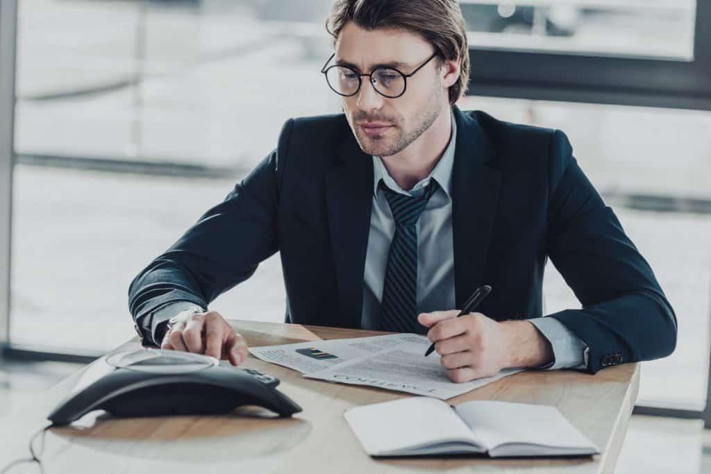 Na foto um homem de terno sentado em uma mesa de reuniões discando em um aparelho de audioconferência.