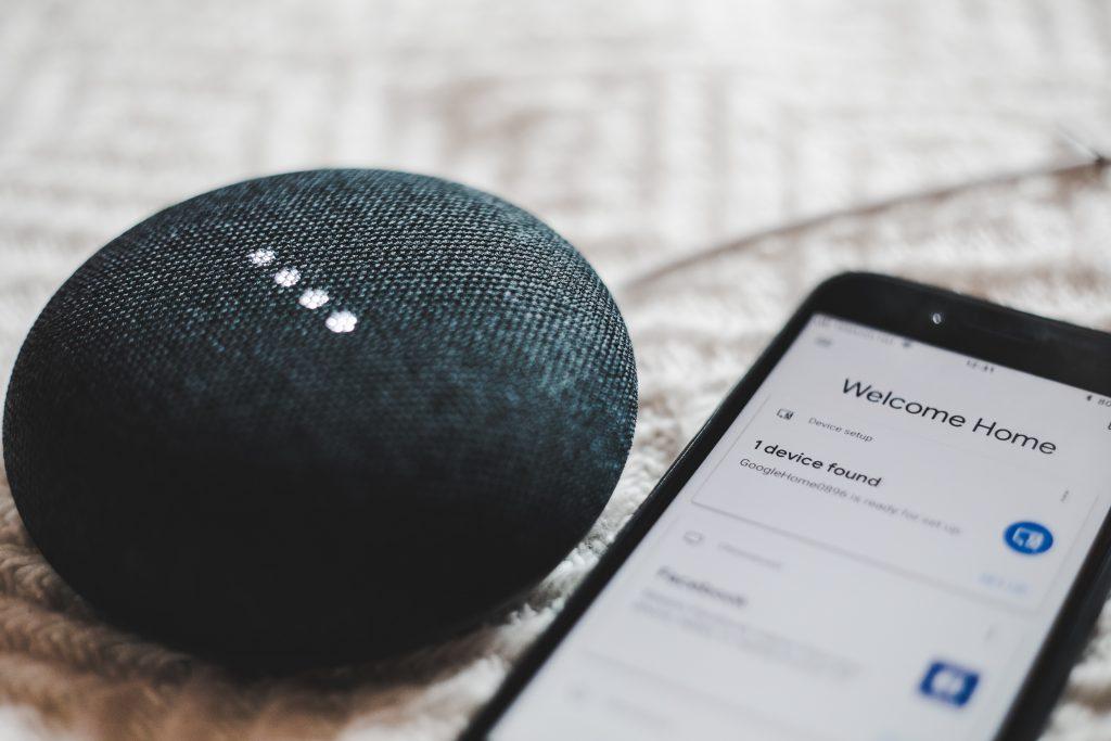 Imagem mostra um close de um smart speaker ao lado de um celular, cuja tela exibe a configuração da conexão com o mesmo smart speaker.