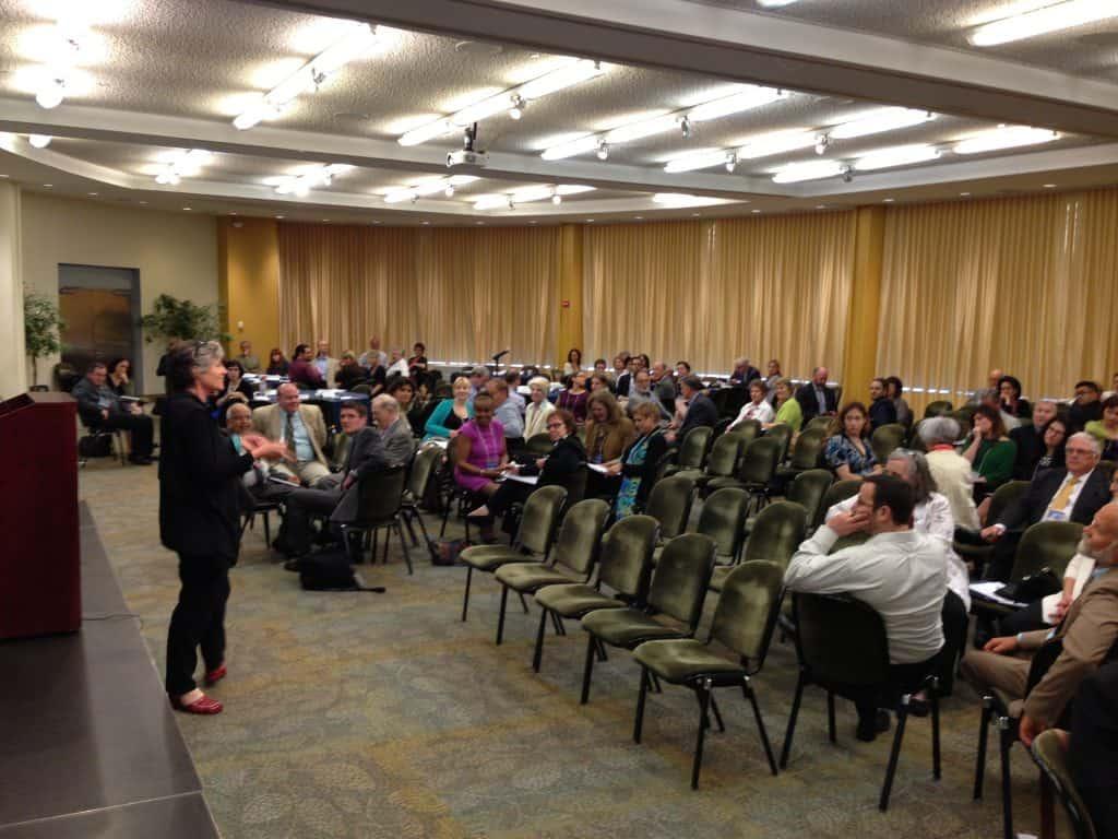 Imagem mostra uma mulher falando em pública perante uma plateia.