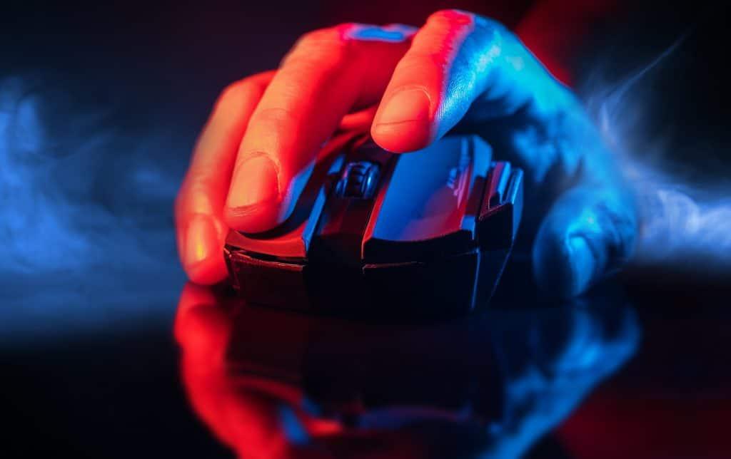 Close de uma mão usando um mouse gamer sem fio.