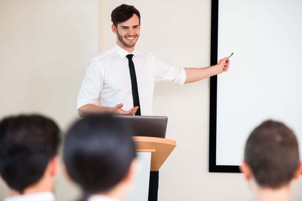 Imagem mostra um homem falando em público perante uma plateia.