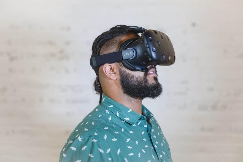 Homem de perfil em sala utilizando o óculos de realidade virtual.