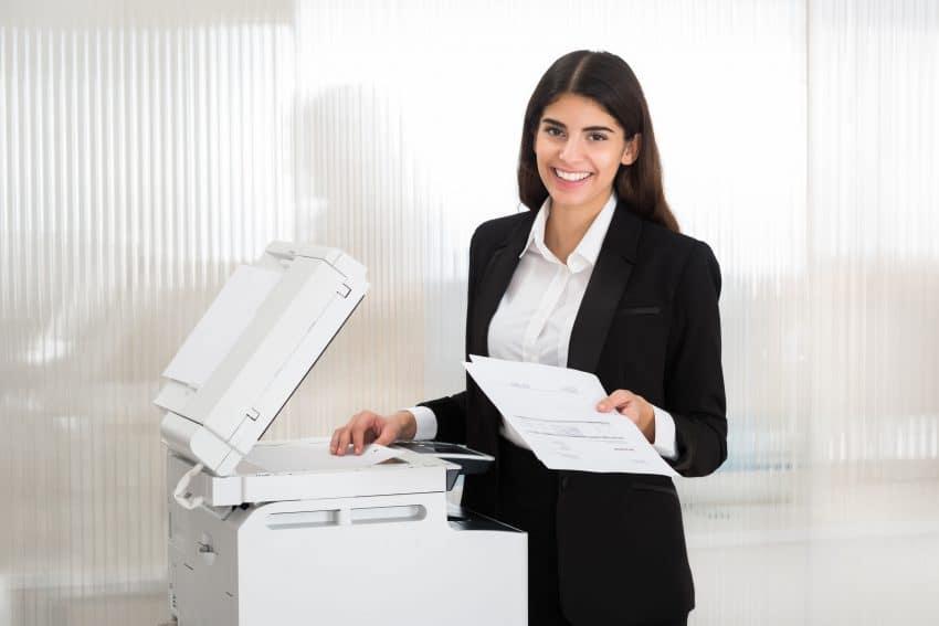 Mulher sorrindo e segurando papeis em frente a impressora laser.