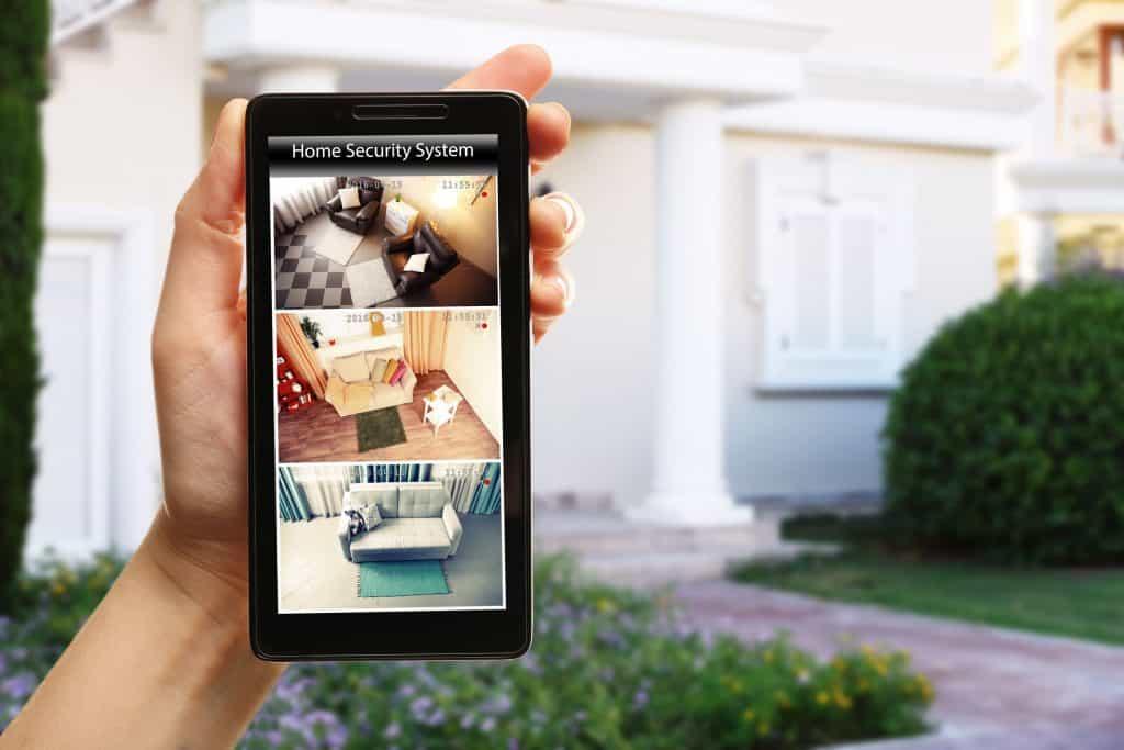 Mão segurando celular com imagens da câmera de segurança, e casa ao fundo.