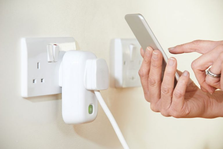 Imagem de pessoa segurando um celular próximo a uma tomada inteligente