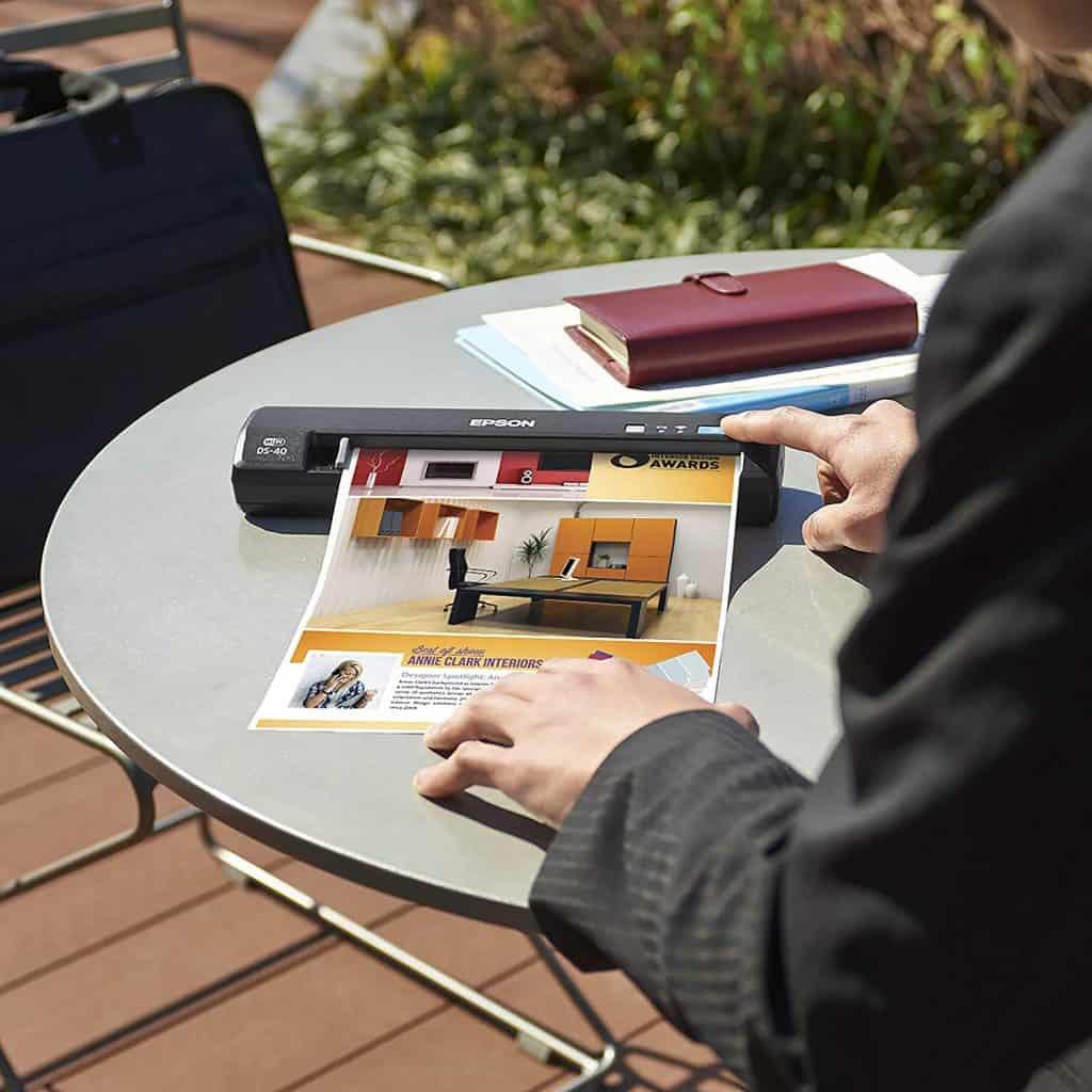 Imagem mostra um homem usando um scanner portátil sobre uma mesa redonda ao ar livre.