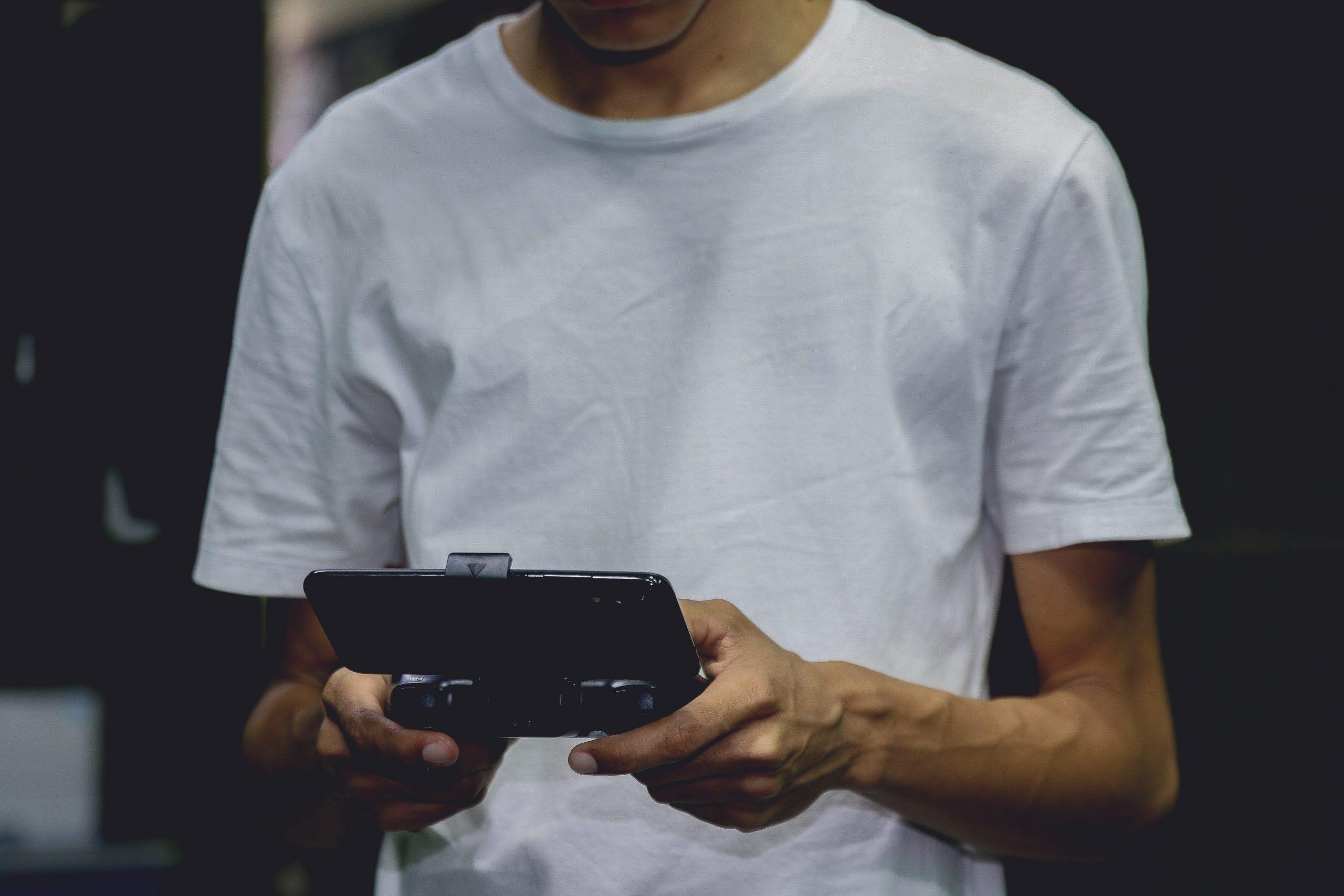 Imagem mostra um homem jogando um game no celular com um gamepad.