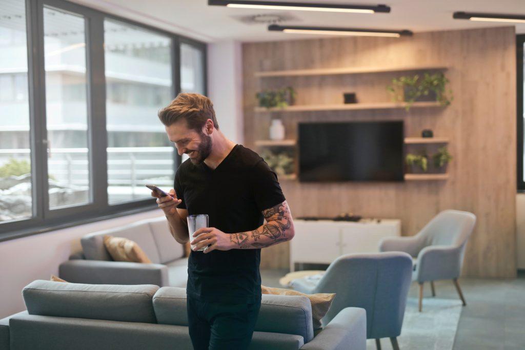Imagem mostra um homem, dentro de um apartamento de amplas janelas, digitando em seu celular com a mão direita. A esquerda segura um copo meio cheio.