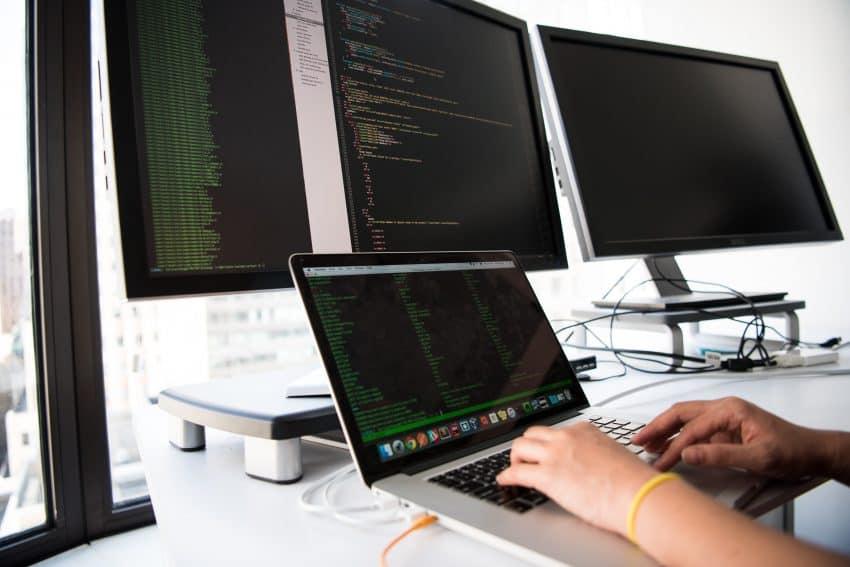 Imagem mostra três monitores sobre uma mesa e mãos digitando no teclado do menor deles.
