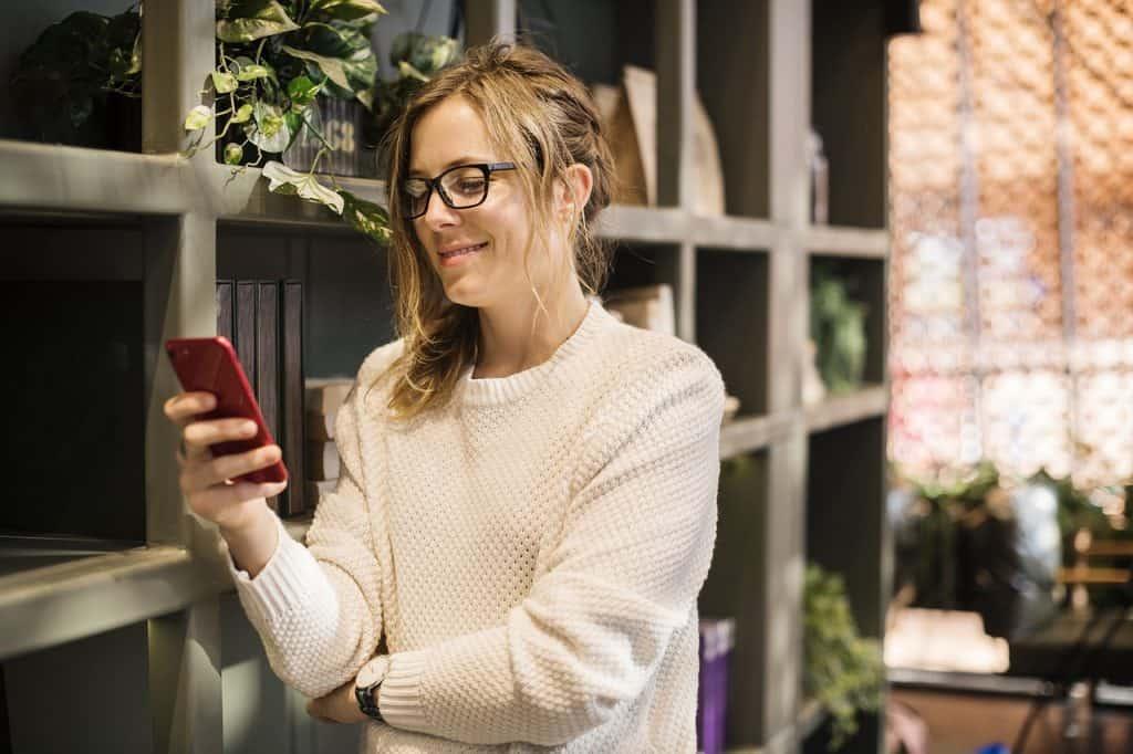 Mulher em pé olhando o celular e sorrindo.