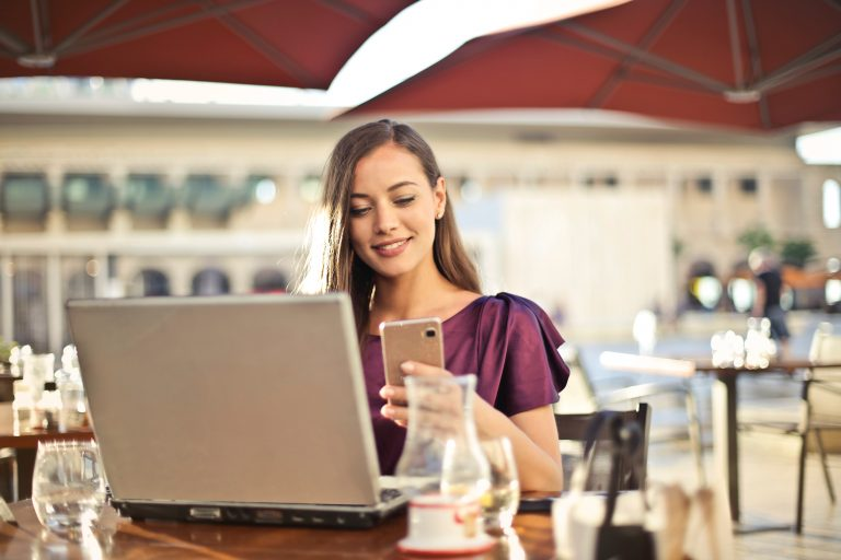 Na foto uma mulher em um restaurante mexendo no celular com um computador na mesa.