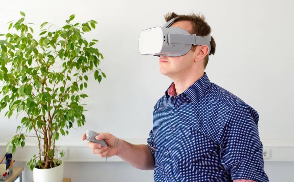 Homem usando óculos de realidade virtual olhando dentro de uma xícara.