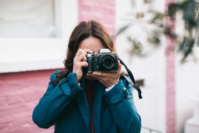Mulher tirando fotografia com câmera Fujifilm.