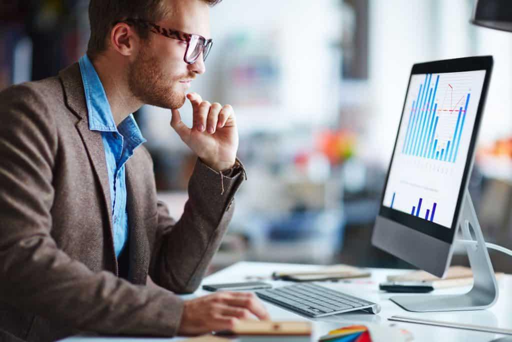Na foto um homem dentro de um escritório em frente a um computador.