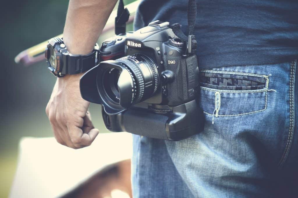 Na foto uma lente Nikon pendurada em um homem de costas.