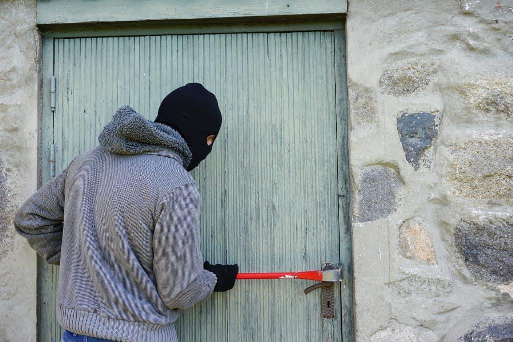 Imagem mostra um ladrão encapuzado tentando abrir uma porta com um pé de cabra.
