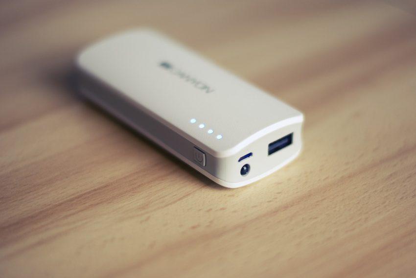 Imagem mostra carregador portátil branco em cima de uma mesa de cor clara.