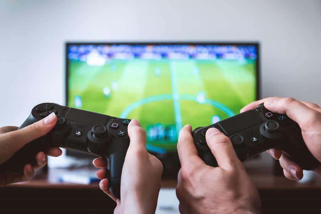Duas pessoas jogando videogame na frente da uma televisão.