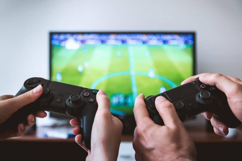 A imagem mostra um homem e uma mulher segurando dois consoles de Playstation e jogando um jogo de videogame.