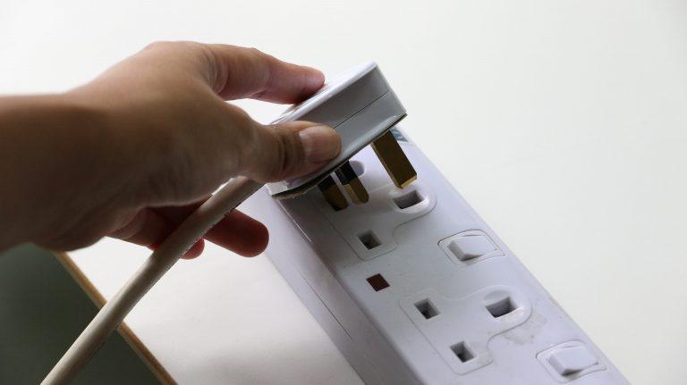 Imagem de pessoa ligando tomada inteligente em uma régua com várias tomadas