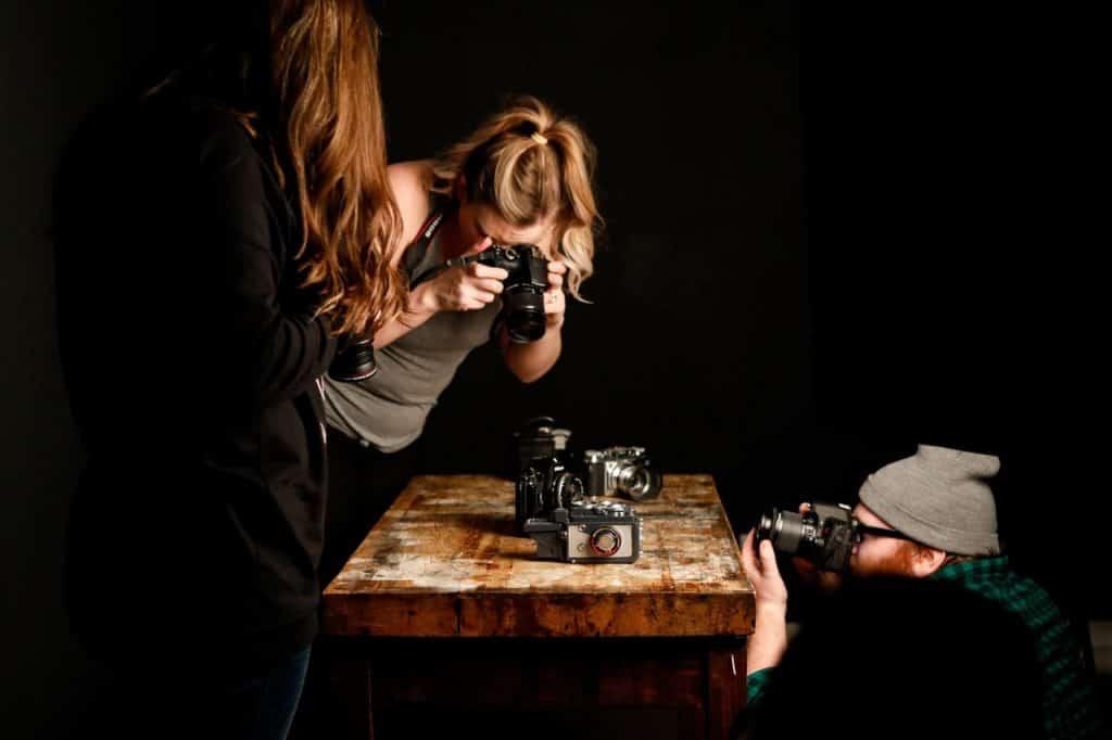 Na foto três fotógrafos juntos fotografando itens em uma mesa.