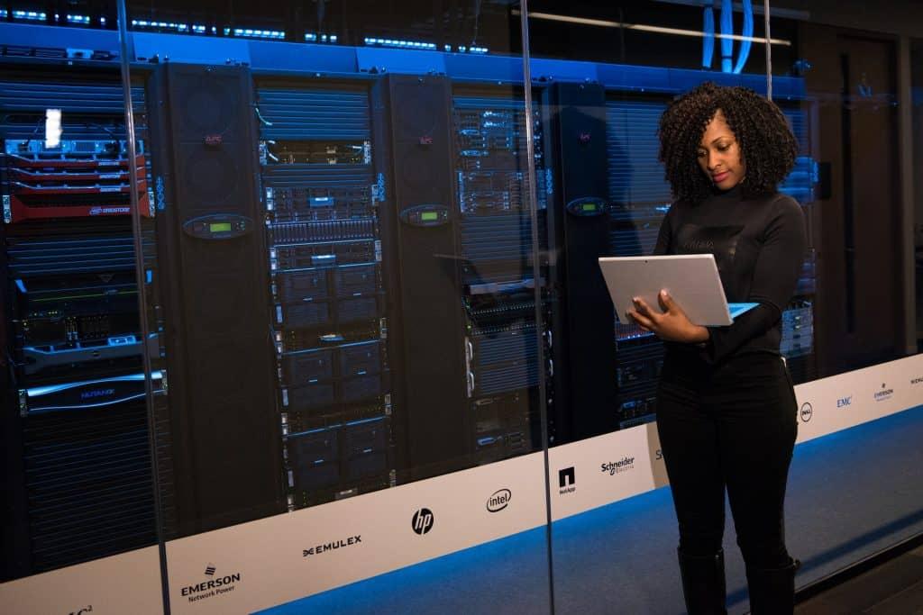 Imagem mostra uma mulher em pé com um notebook em frente a um enorme sistema de armazenamento.