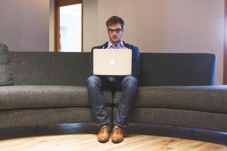 Homem sentado em sofá usando notebook.