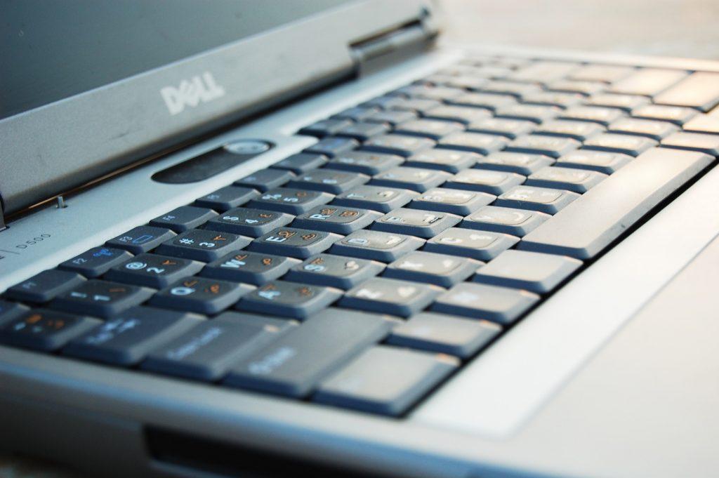 Notebook Dell prata em close, mostrando seu teclado e o logo da Dell.