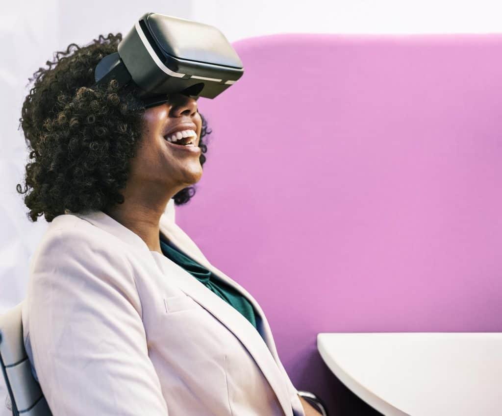 Mulher rindo sentada em uma cadeira sobre fundo rosa utilizando o óculos de realidade virtual.