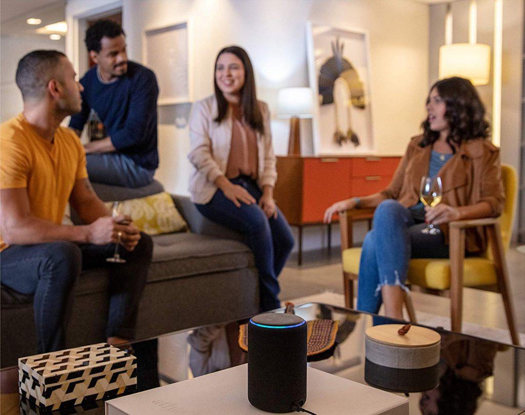Imagem de um grupo de pessoas reunidas, na mesa há um dispositivo Echo.